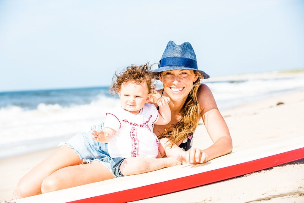Emily Tyson with her daughter at the beach on a surfboard.