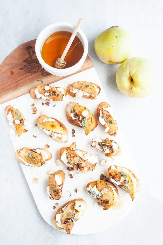 Pear and goat cheese crostini on a white platter with a small bowl of honey.