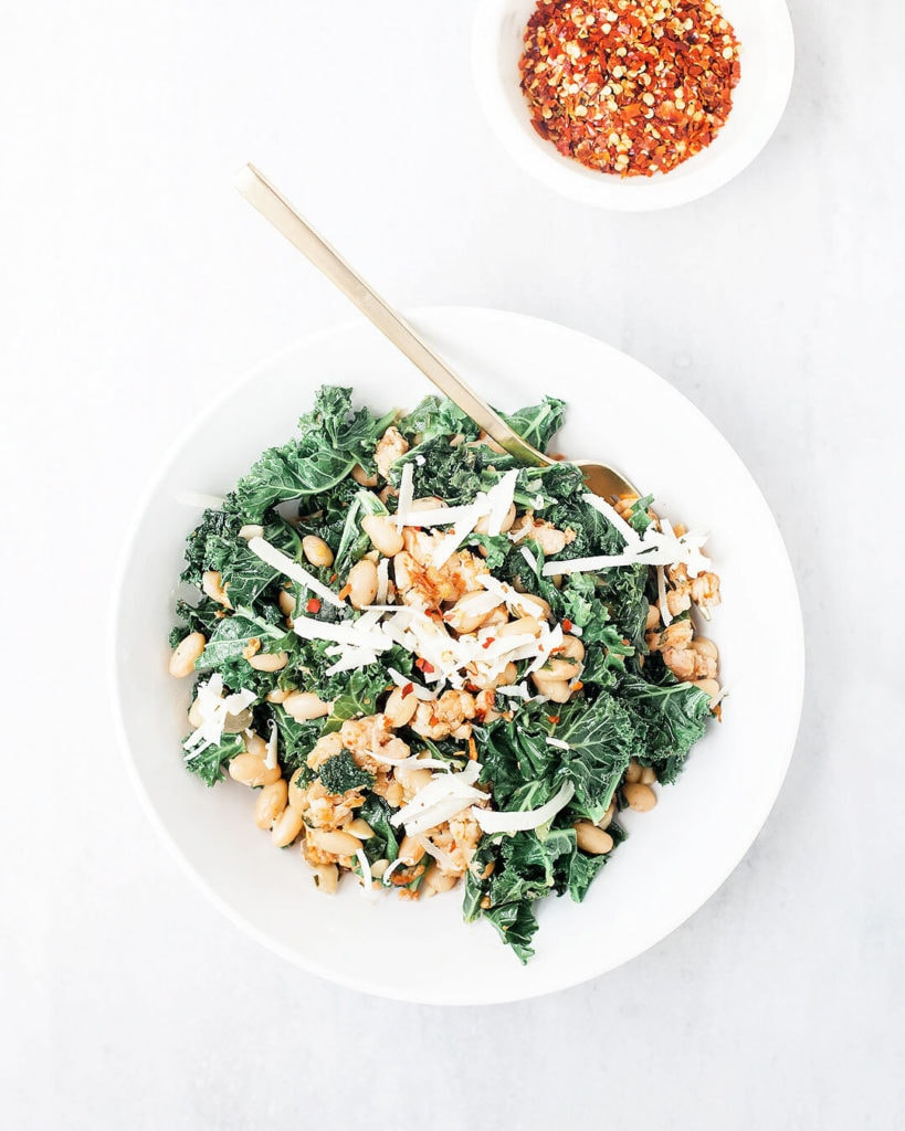 Tuscan beans with sausage and kale in a white bowl.