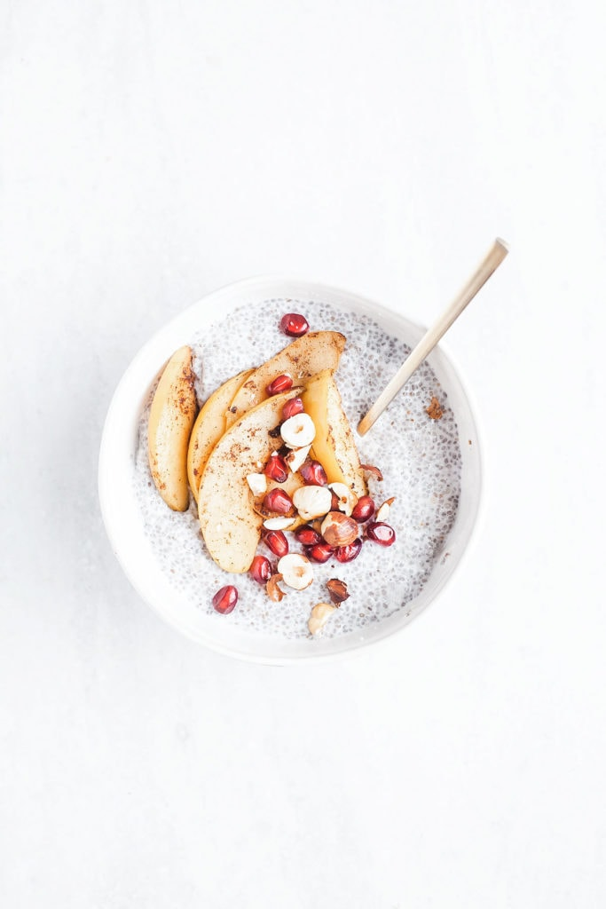 Pear chia pudding in a white bowl with pear slices and pomegranate seeds.