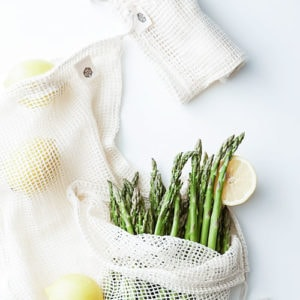 Mesh produce bags with asparagus and lemons.