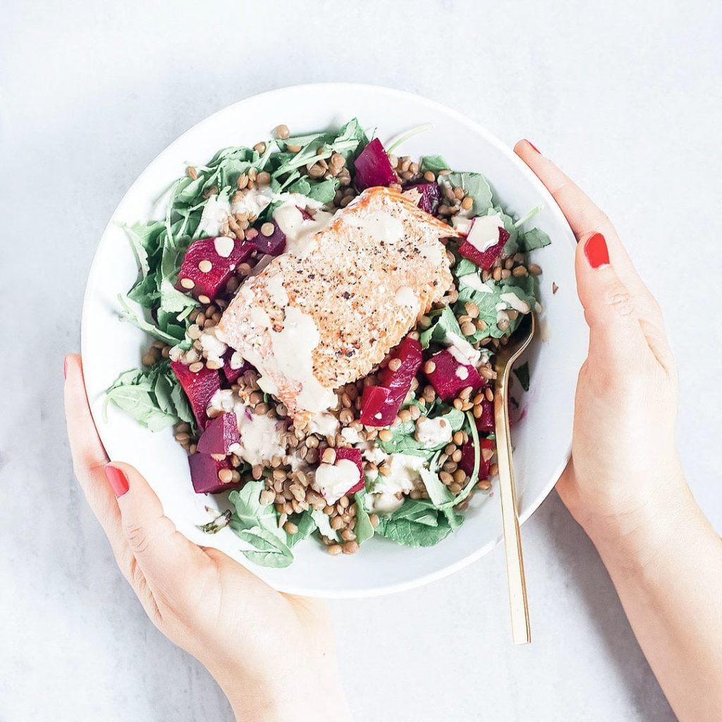 Beet and salmon salad in a white bowl being held by hands.
