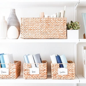 Baskets on a shelf with white bin clip labels.