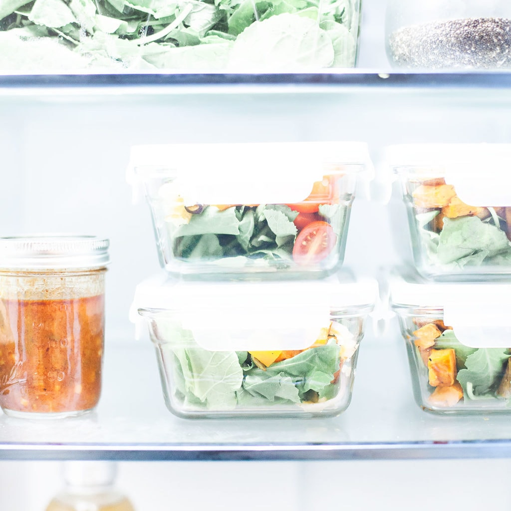 Glass containers full of salads stacked in a clean fridge.