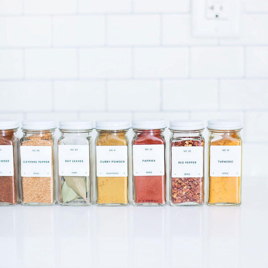 Organized spices lined up on a kitchen counter with white subway tile behind.