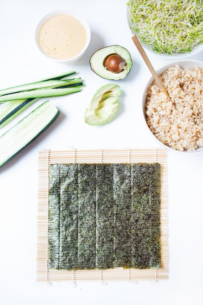 A sheet of nori on a sushi mat with avocado vegan sushi ingredients.