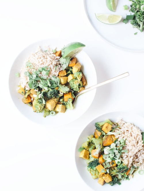 Broccoli and sweet potato curry with brown rice in white bowls.