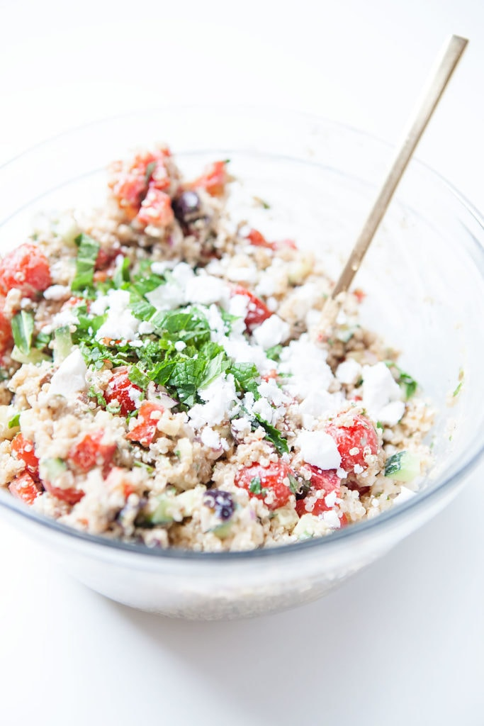 Greek quinoa salad with feta cheese and mint in a glass bowl.