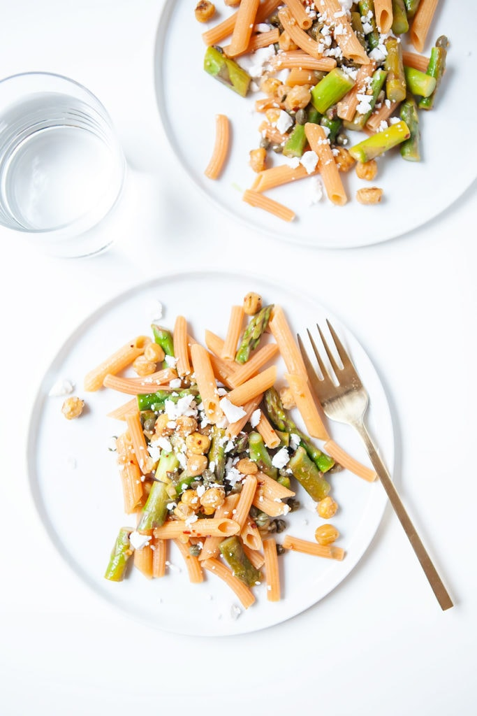 Red lentil pasta with asparagus, capers, and chickpeas on two white plates and a glass of water.