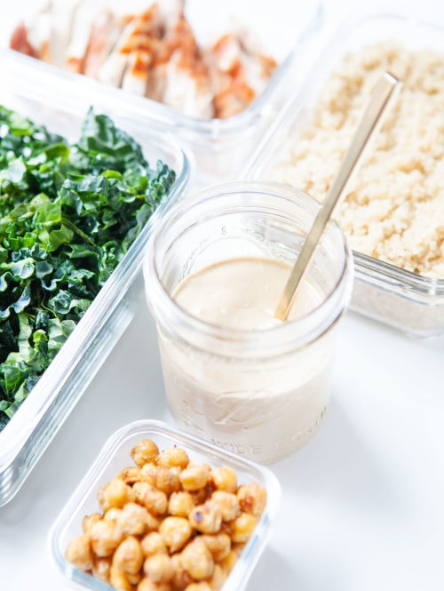 Grilled chicken, quinoa, kale, tahini sauce, and crispy chickpeas in meal prep containers on a white background.
