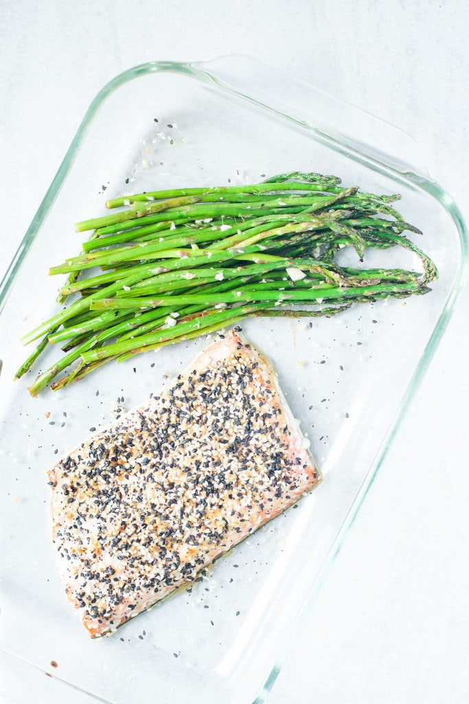 Everything bagel salmon with asparagus in a glass baking dish.