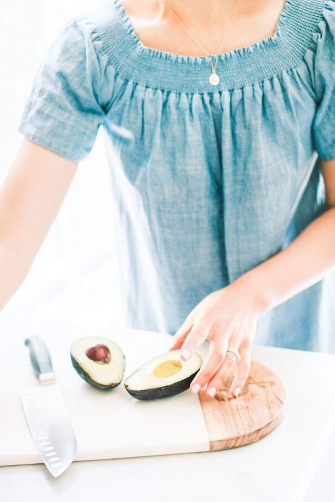 Woman in blue dress cutting an avocado.
