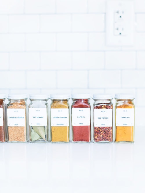 Uniform spice jars with modern spice labels lined up on a white kitchen counter.