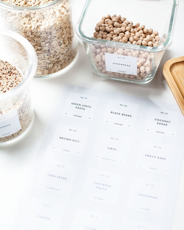 Printed pantry labels and glass jars filled with pantry ingredients.