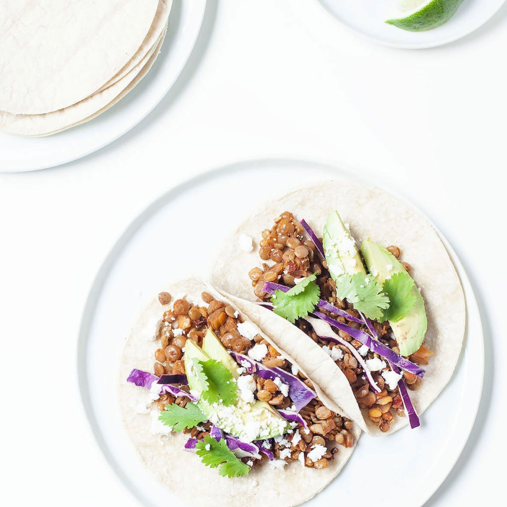 Lentil tacos on a white plate with avocado and limes.