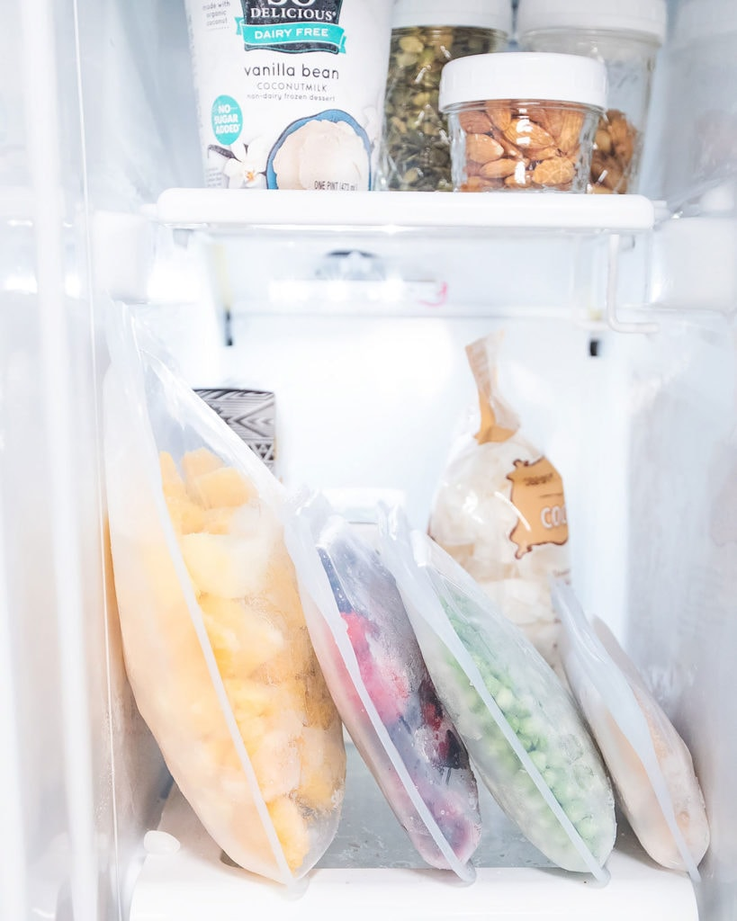 Organized freezer with Stasher bags full of frozen fruit.