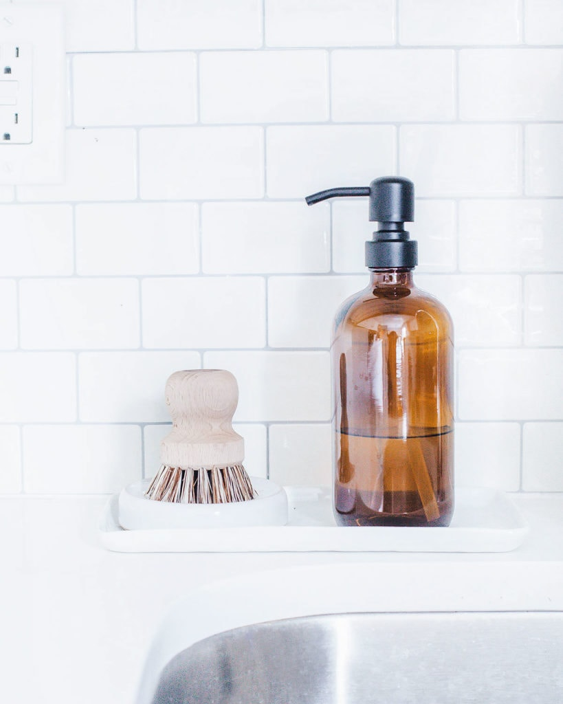 Dish brush and amber glass soap dispenser next to a sink.