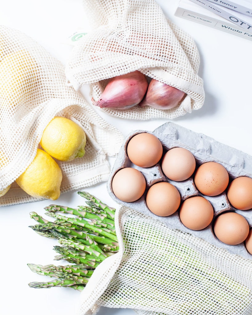 Produce in mesh cotton bags and a carton of eggs.