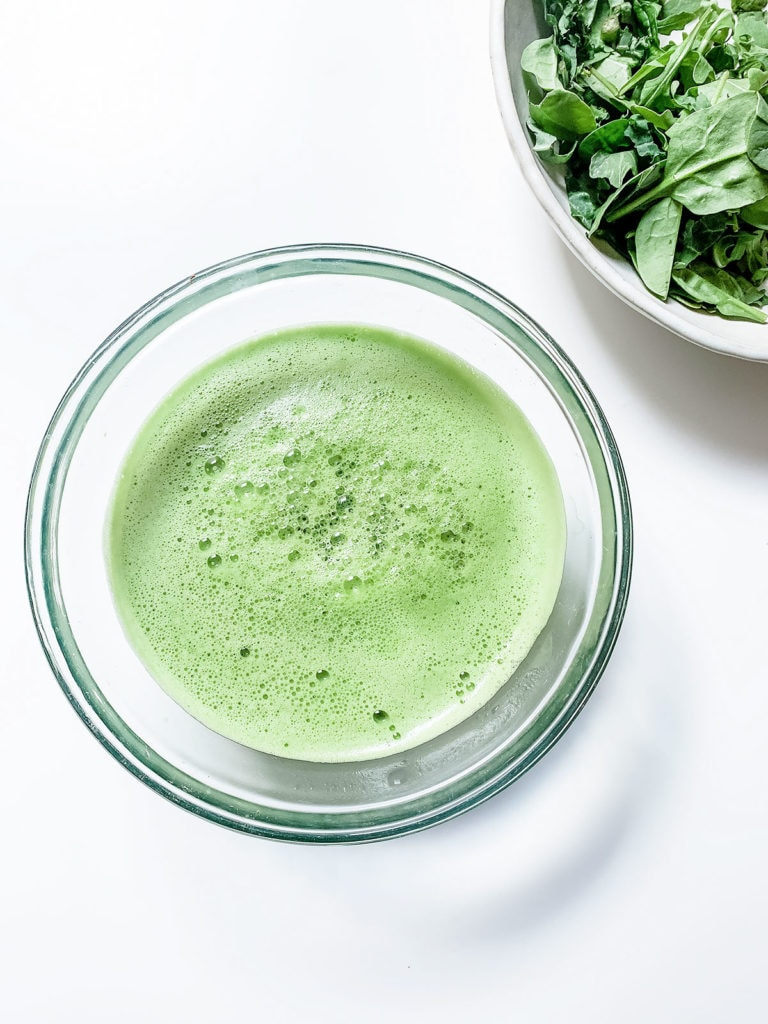 Blender green juice in a bowl with a bowl of greens next to it.