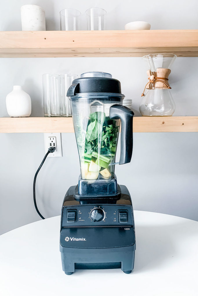 Blender full of blender green juice ingredients with open shelving in the background.