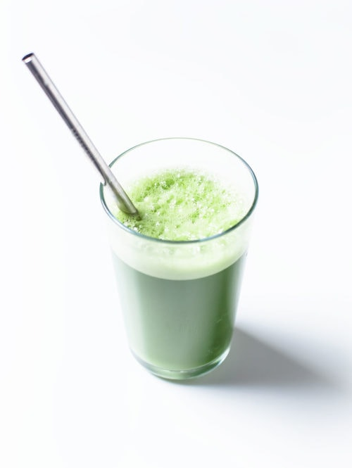 Glass of blender green juice with a metal straw.