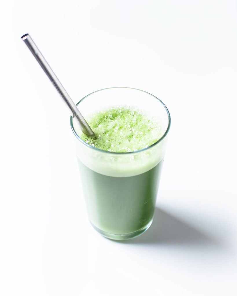 Blender green juice in a glass with a straw.