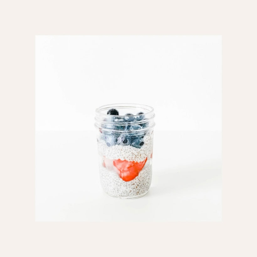 July 4th chia pudding in a jar with strawberries and blueberries.