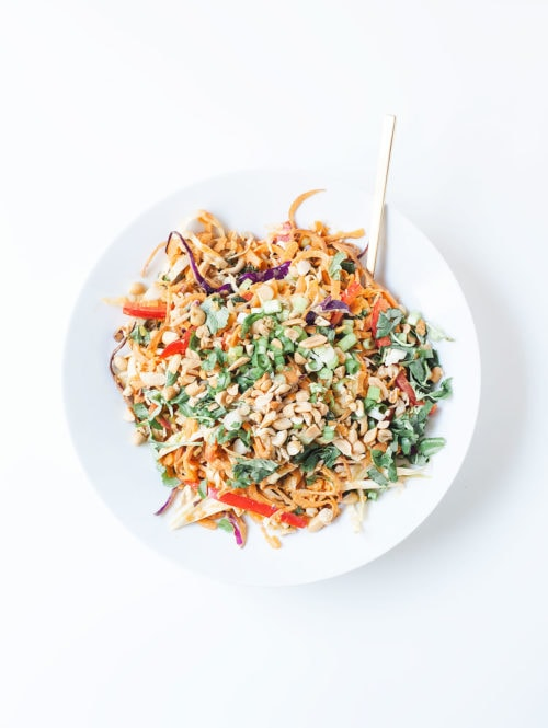 Sweet potato noodle bowls with coconut peanut sauce in a white bowl.