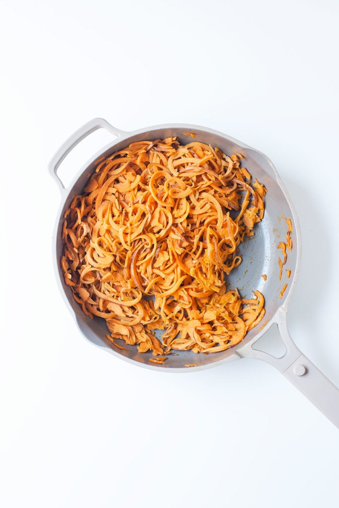 Spiralized sweet potato noodles in a pan on a white table.
