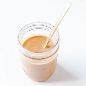 Coconut peanut sauce in a jar with a spoon.