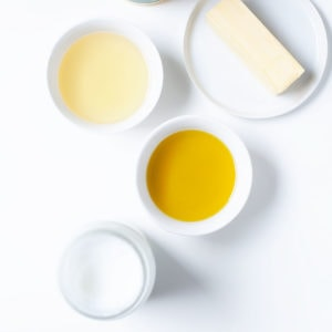 Cooking fats and oils in white containers on a white background.