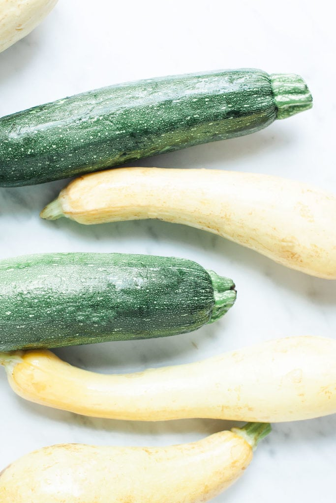 Zucchini and yellow summer squash on a white table.